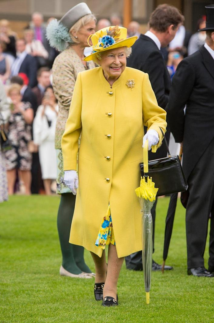 <p>Queen Elizabeth looked sunny in yellow for a garden party at Buckingham Palace—even her umbrella matched her outfit. </p>