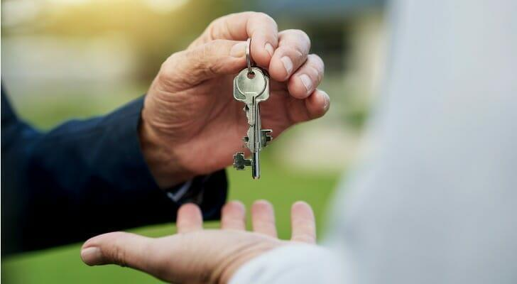 Housekeys being handed from one person to another