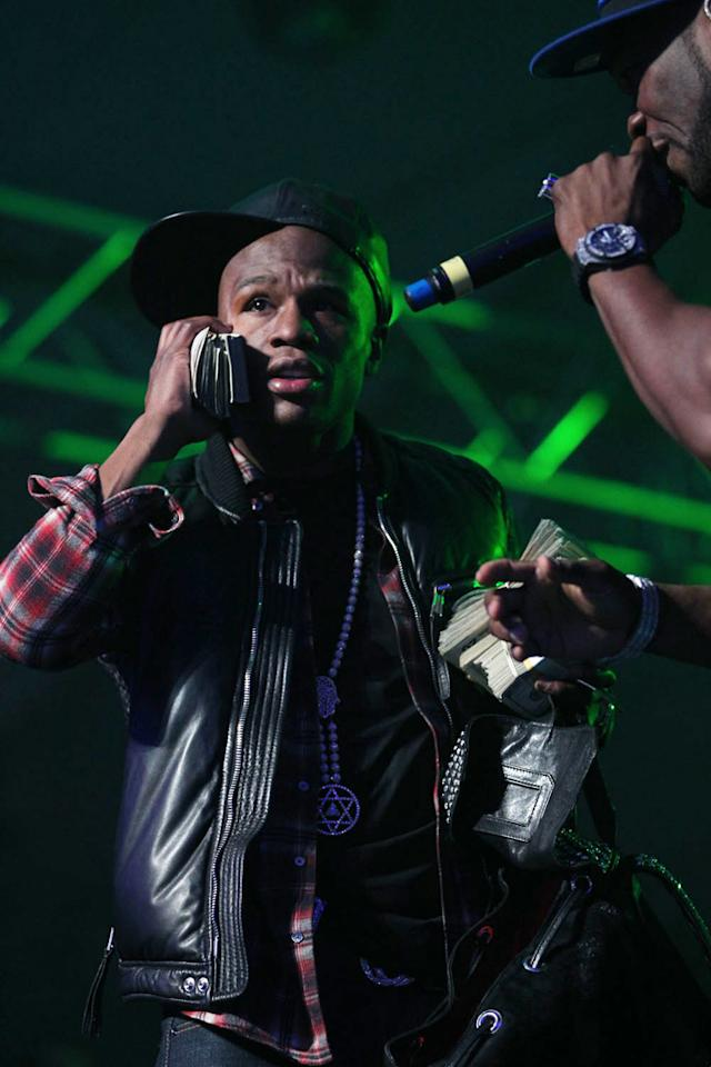 Floyd Mayweather throws cash on stage as 50 Cent performs at the Bud Light Hotel concert.
