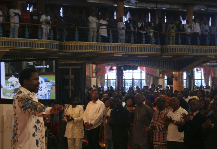 FILE - In this Sunday, Sept. 15, 2013 file photo, T.B. Joshua, left, conducts a service at the Synagogue, Church of All Nations, in Lagos Nigeria. One of Africa's most popular televangelists, T.B. Joshua, has died, according to his church. He was 57. The Nigerian-born pastor was founder of the mega church, Synagogue Church Of All Nations (SCOAN) which also runs the Emmanuel Television Station in Lagos, Nigeria. The church announced his death in a statement Sunday, June 6, 2021. Joshua was noted for making predictions and for his claims to cure various ailments and to make people prosper through miracles. (AP Photo/Carley Petesch, File)