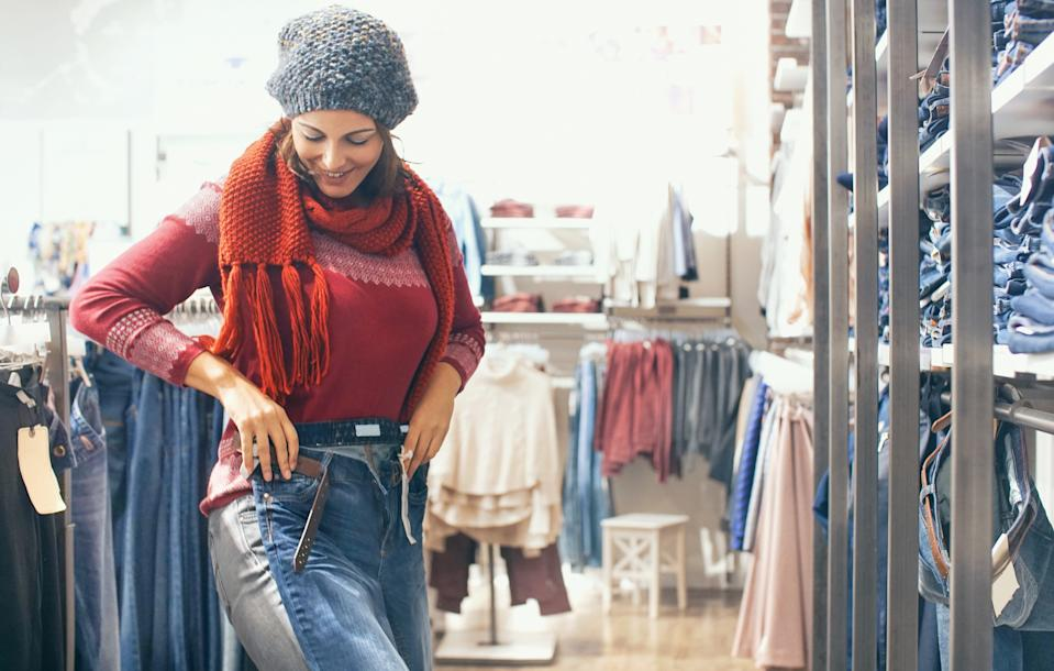Closeup of smiling adult woman trying on new pair of jeans in shopping mall. She has put the pants over her legs to se if they fit. She's wearing red cardigan and scarf and gray hair. There are many different jeans around her.