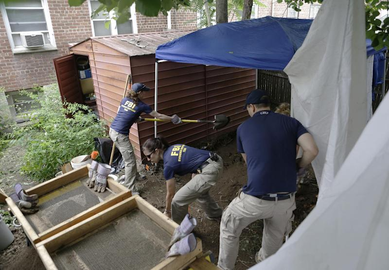 "FBI agents replace dirt after searching in the backyard of a New York city house once occupied by a famous gangster, Tuesday, June 18, 2013, in New York.  The work started Monday at the home of James Burke, a Lucchese crime family associate known as ""Jimmy the Gent."" He was the inspiration for Robert De Niro's character in the 1990 Martin Scorsese movie ""Goodfellas."" Burke died behind bars in 1996, two decades after authorities say he masterminded a nearly $6 million robbery at New York's Kennedy Airport, one of the largest cash thefts in American history. The Queens house is still owned by the Burke family, but others now live there. (AP Photo/Kathy Willens)"