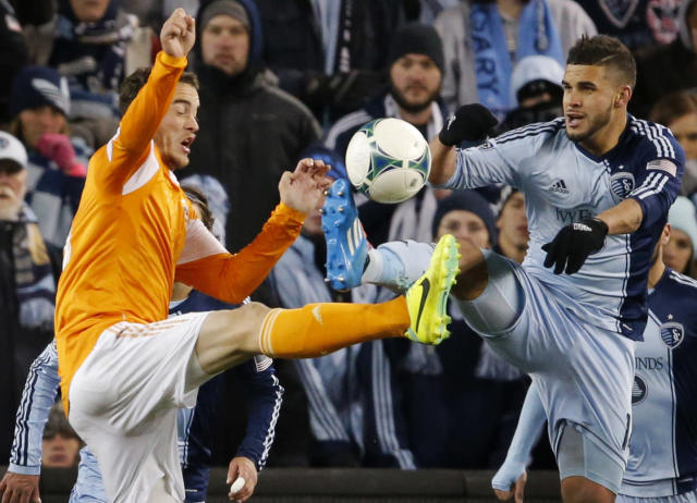 Houston defender Eric Brunner, left, and Sporting KC forward Dom Dwyer, right, battle for the ball during the second half of an MLS playoff soccer match in Kansas City, Kan., Saturday, Nov. 23, 2013. Sporting KC defeated Houston Dynamo 2-1. (AP Photo/Orlin Wagner)