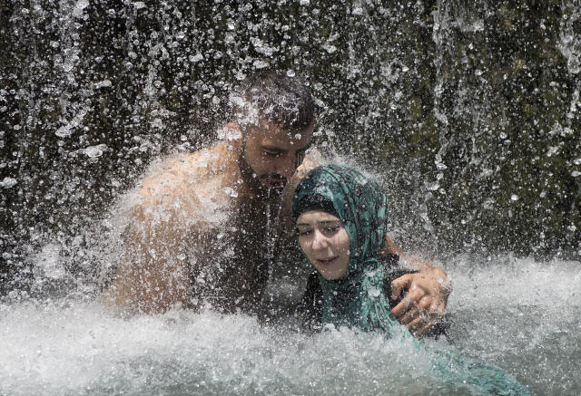 <p>Israeli Arabs stand under a waterfall during the Eid al-Fitr holiday at the Gan HaShlosha national park near the northern Israeli Town of Beit Shean, July 8, 2016. (Photo: Oded Balilty/AP) </p>