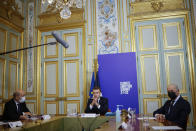 FILE - In this Dec. 12, 2020, file photo, French President Emmanuel Macron, center flanked by French Foreign Minister Jean-Yves Le Drian, left, and President of the French Constitutional Council Laurent Fabius, right, speaks during the Climate Ambition Summit 2020 video conference at the Elysee Palace in Paris. World leaders are applauding Friday's formal return of the U.S. to the mostly voluntary 2015 agreement, saying it is symbolic and important. They say they expect the United States to show leadership in the fight against warming by setting strong targets for carbon pollution cuts by 2030.(Yoan Valat, Pool via AP)