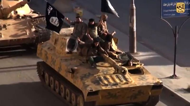 A screen grab taken from a video released on July 1, 2014, by Welayat Raqa allegedly shows members of the Islamic State group parading on top of a tank in the northern Syrian city of Raqa (AFP Photo/)