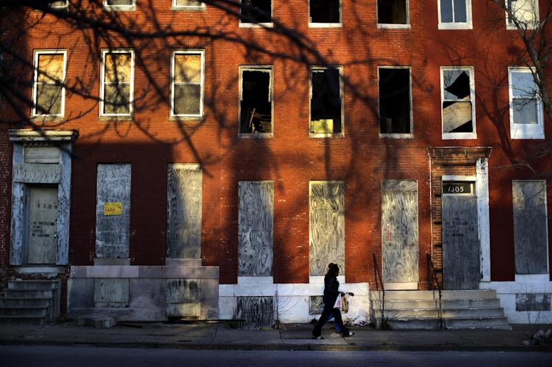 In this March 30, 2013 picture, a woman walks past blighted row houses in Baltimore. Baltimore is far from the worst American city for poverty, but it faces all the problems of cities where vast numbers of the poor now live. The U.S. Census Bureau puts the number of Americans in poverty at levels not seen since the mid-1960s, while $85 billion in federal government spending cuts that began last month are expected to begin squeezing services for the poor nationwide. (AP Photo/Patrick Semansky)