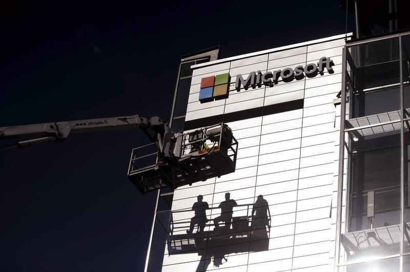 Workers install the logo of U.S. technology giant Microsoft on the wall of Nokia's former headquarters in Espoo