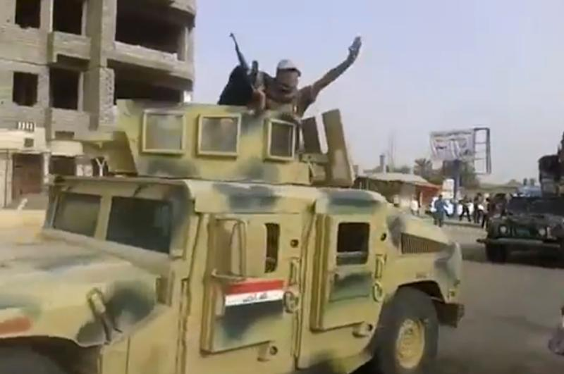 An image grab taken from a video uploaded on YouTube on June 17, 2014, allegedly shows militants from the Islamic State of Iraq and the Levant (ISIL) parading with an Iraqi army vehicle in the northern city of Baiji
