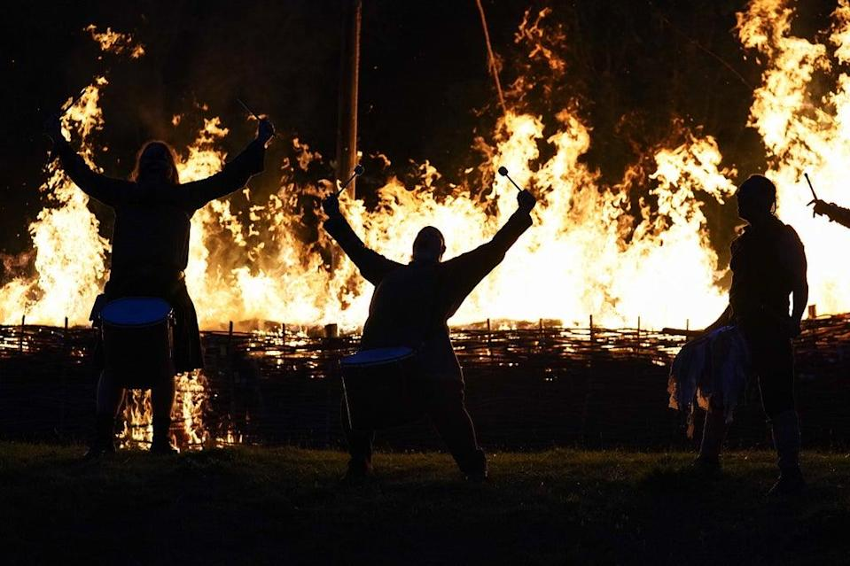 Pentacle Drummers play in front of a burning ceremonial Viking long boat at Butser Ancient Farm in Hampshire, to mark the autumn equinox (PA)