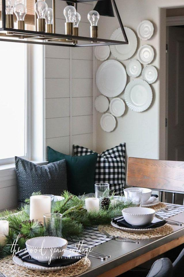 """<p>A strip of black and white window pane fabric straight from the store serves as the foundation for this cute Christmas brunch setting. No sewing required!</p><p><strong>Get the tutorial at <a href=""""https://www.thewoodgraincottage.com/2017/12/04/christmas-table-setting-breakfast-nook/"""" rel=""""nofollow noopener"""" target=""""_blank"""" data-ylk=""""slk:The Wood Grain Cottage"""" class=""""link rapid-noclick-resp"""">The Wood Grain Cottage</a>.</strong></p><p><a class=""""link rapid-noclick-resp"""" href=""""https://go.redirectingat.com?id=74968X1596630&url=https%3A%2F%2Fwww.ikea.com%2Fus%2Fen%2Fcatalog%2Fproducts%2F00342876%2F&sref=http%3A%2F%2Fwww.countryliving.com%2Fdiy-crafts%2Fg644%2Fchristmas-tables-1208%2F"""" rel=""""nofollow noopener"""" target=""""_blank"""" data-ylk=""""slk:SHOP WOVEN PLACEMATS"""">SHOP WOVEN PLACEMATS</a></p>"""