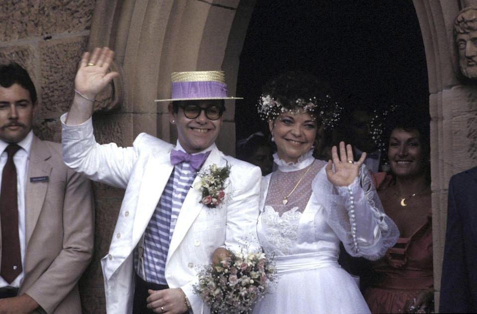 <p>Sir Elton John and his wife Renate wave to the crowd as they exit their wedding ceremony on Valentine's Day in 1984. He remained with the German recording engineer until their divorce in 1988. He later went on to marry advertising exec David Furnish in 2014.</p>