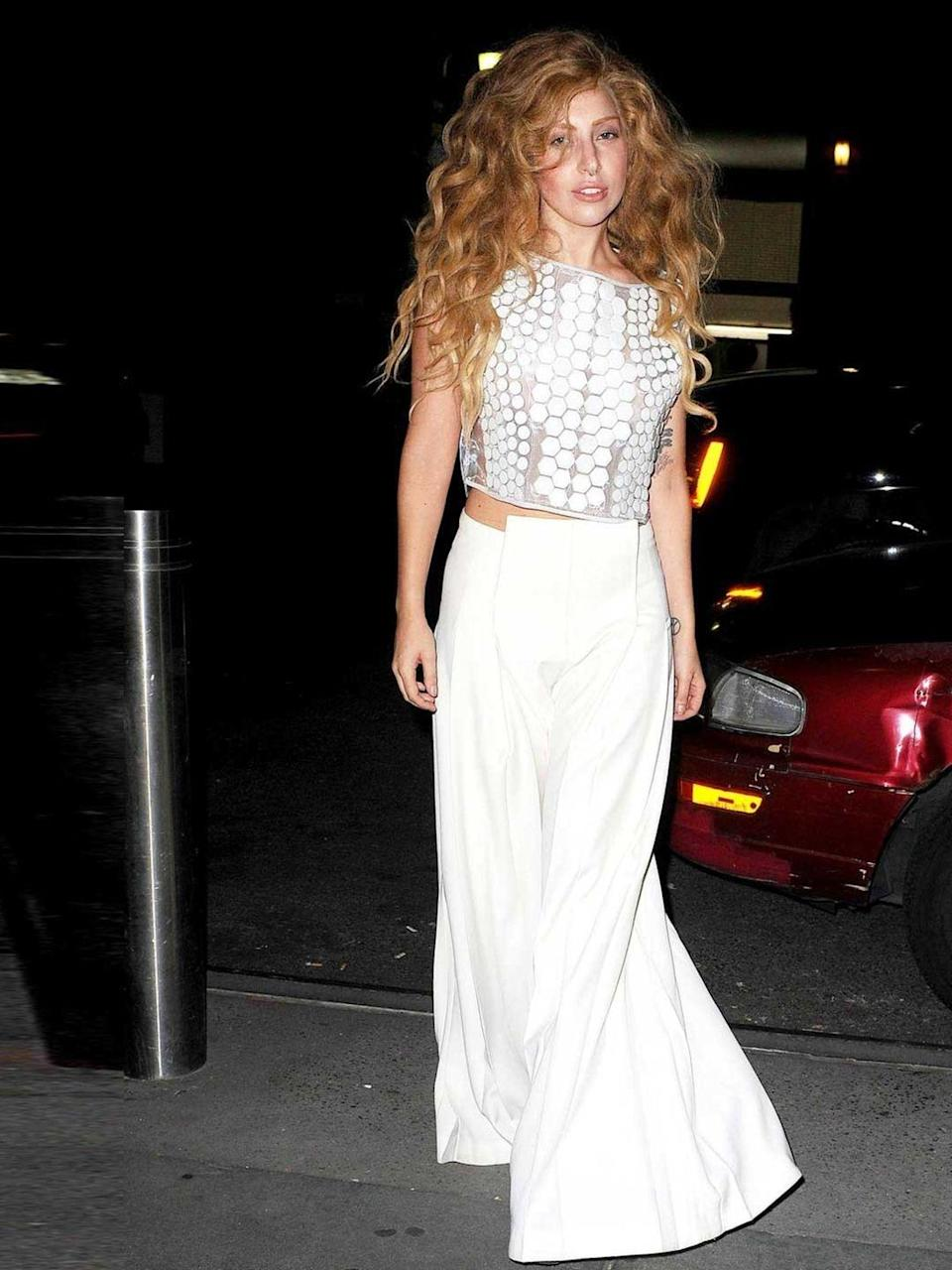 <p>Lady Gaga wore crop top with high-waisted trousers as she left the recording studio in New York, August 2013. </p>