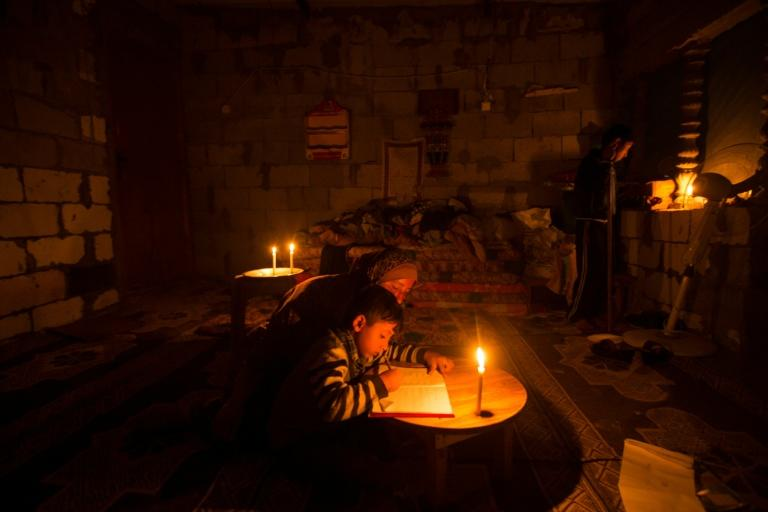 A Palestinian woman helps her son study, by candlelight, at their makeshift home in the Khan Yunis refugee camp in the southern Gaza Strip on April 19, 2017