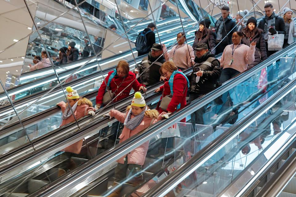 People ride an escalator in H & M during a Black Friday sales event in Manhattan, New York City, U.S., November 23, 2018. REUTERS/Andrew Kelly