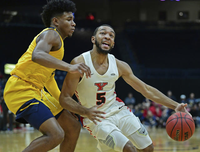 Youngstown State guard Christian Bentley (5) drives on West Virginia guard Miles McBride (4) during the first half of an NCAA college basketball game, Saturday, Dec. 21, 2019, in Youngstown, Ohio. (AP Photo/David Dermer)