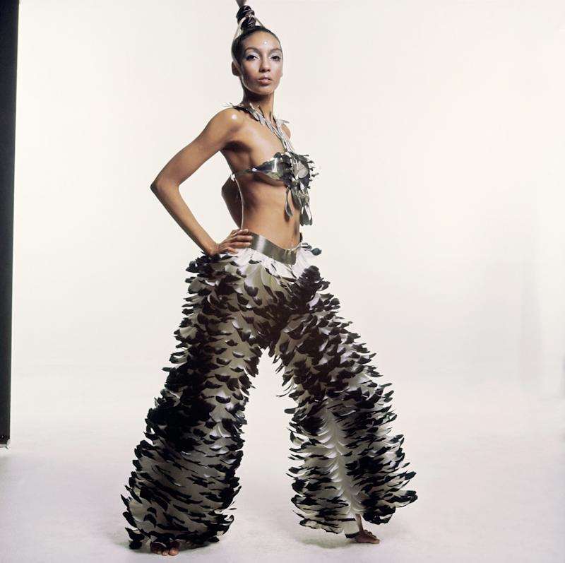 Model Carol La Brie wearing an Emanuel Ungaro ensemble: a necklace and brassiere of silver steel body jewelry in one piece; wide pants of white feathers with black tips and a silver steel waistband. Makeup and hair by Carita. Model's hair is pulled up into an elaborate up-do.