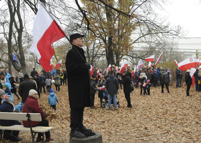 People gather in a park to watch the official ceremony marking Poland's Independence Day, in Warsaw, Poland, Sunday, Nov. 11, 2018. The Independence Day in Poland celebrates the nation regaining its sovereignty at the end of World War I after being wiped off the map for more than a century. (AP Photo/Alik Keplicz)