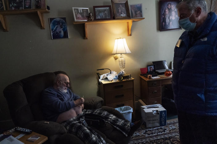 """George Dean, 74, gives himself an insulin injection as Meals on Wheels of Rhode Island driver Jim Stotler brings him a meal at his home in Cumberland, R.I, Friday, Nov. 20, 2020. """"He takes a lot off my mind when he comes in,"""" said Dean, a diabetic who has come to rely on Stotler's weekday visits as he's had fewer visitors and doesn't go out as much since the pandemic started. """"He comes whether you're sick or not, asks how you're feeling and tells a joke every now and then."""" (AP Photo/David Goldman)"""