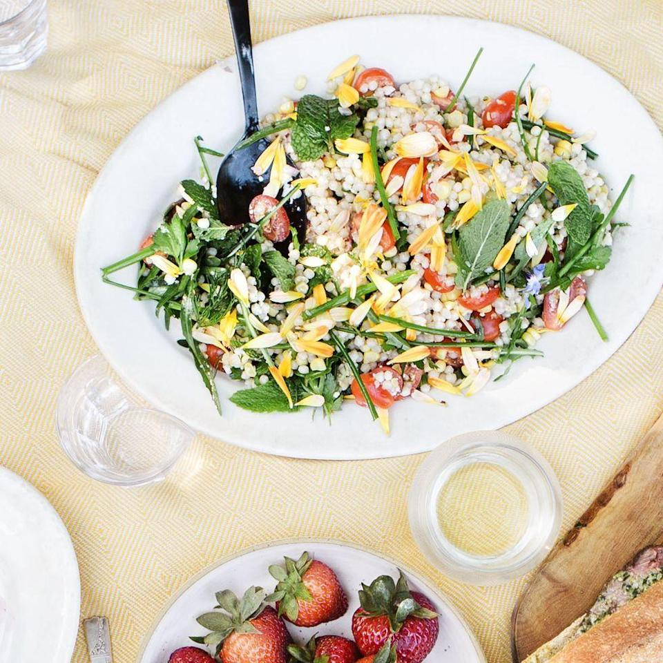 """<p>Showcase your tasty and colorful veggies in this pasta salad that's bound to be your new favorite go-to lunch. It's quick (read: only takes 20 minutes), delicious, and easy. </p><p><em><a href=""""https://www.womansday.com/food-recipes/a32884015/fresh-corn-tomato-herb-and-israeli-couscous-salad-recipe/"""" rel=""""nofollow noopener"""" target=""""_blank"""" data-ylk=""""slk:Get the Fresh Corn, Tomato, Herb, and Israeli Couscous Salad recipe."""" class=""""link rapid-noclick-resp"""">Get the Fresh Corn, Tomato, Herb, and Israeli Couscous Salad recipe.</a></em></p>"""