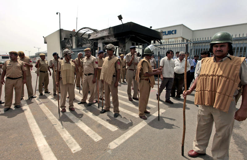 Policemen stand at the Maruti Suzuki factory a day after workers rioted in Manesar, on the outskirts of New Delhi, India, Thursday, July 19, 2012. Top Indian carmaker Maruti Suzuki has shut the factory after rioting killed one person and injured dozens of others.(AP Photo/ Saurabh Das)
