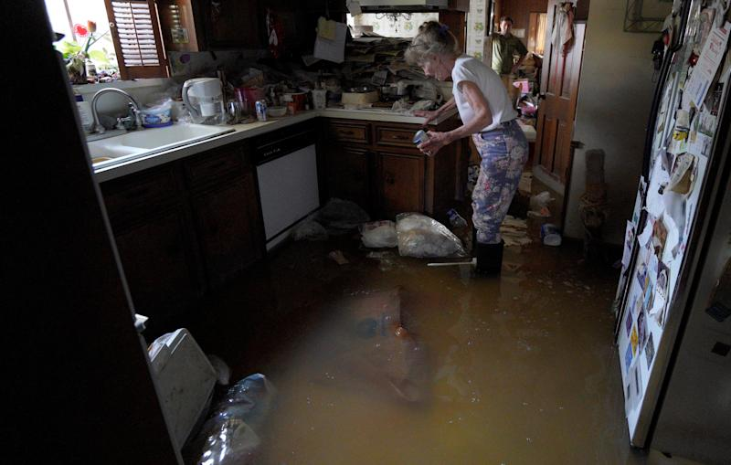 Nancy McBride collects items from her flooded kitchen as she returned to her home on Sept. 1, 2017, for the first time since floods caused by Hurricane Harvey inundated Houston.<i></i> (Rick Wilking / Reuters)