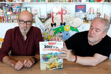 """Author Jean-Yves Ferri and illustrator Didier Conrad hold a copy of their new comic album """"Asterix et la Transitalique"""" (Asterix and the Chariot Race) during an interview in Vanves near Paris"""