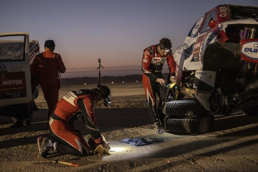 Driver Fernando Alonso, of Spain, center, and co-driver Marc Coma, of Spain, right, repair their Toyota after rolling over during the stage ten of the Dakar Rally between Haradth and Shubaytah, Saudi Arabia, Wednesday, Jan. 15, 2020 photo. (AP Photo/Bernat Armangue)