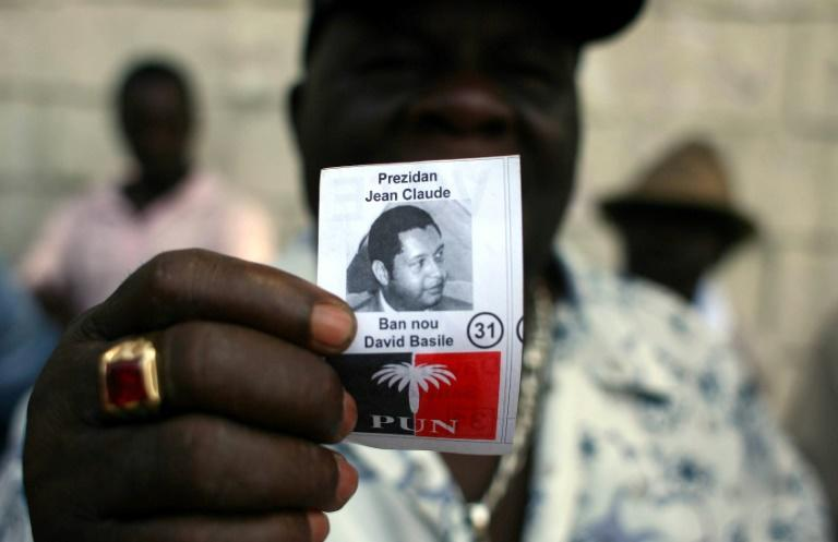 "A former member of Tonton Macoute paramilitary force displays a photograph of Jean-Claude ""Baby Doc"" Duvalier while on guard outside a private hospital in Port-au-Prince where the ex-dictator was being treated in 2011"