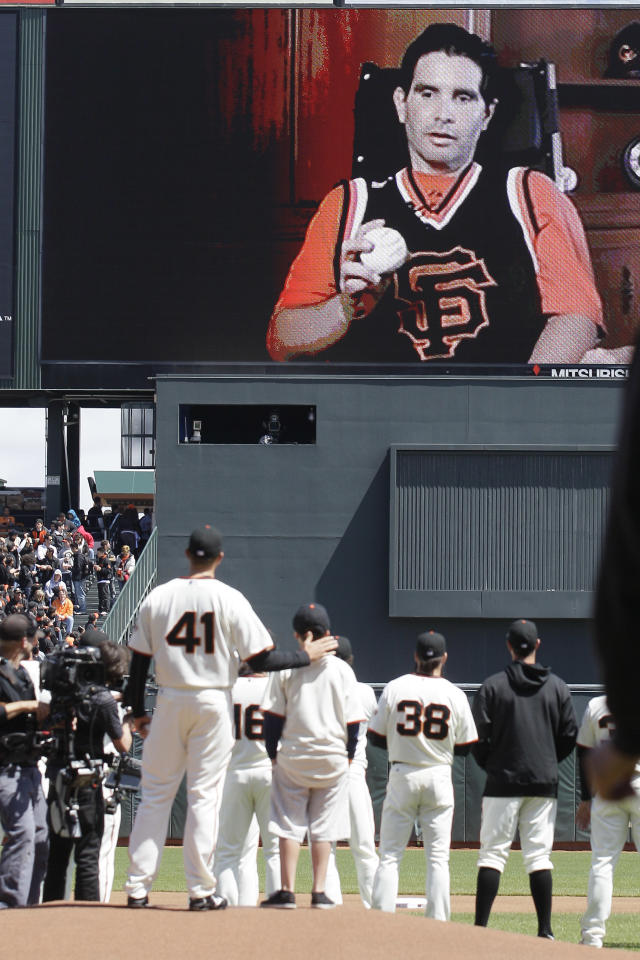 Tyler Stow, son of Bryan Stow, who was beaten last year at Dodger Stadium, looks up and listens to his father on a big screen before throwing out the ceremonial first pitch of the San Francisco Giants Opening Day baseball game against the Pittsburgh Pirates in San Francisco, Friday, April 13, 2012. Standing with Tyler Stow is Giants pitcher Jeremy Affeldt (41). (AP Photo/Jeff Chiu)