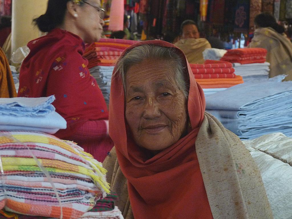 This elderly Ima has been selling phaneks and shawls for many years at the Ima Market, long before it moved to these spacious galleries of concrete.
