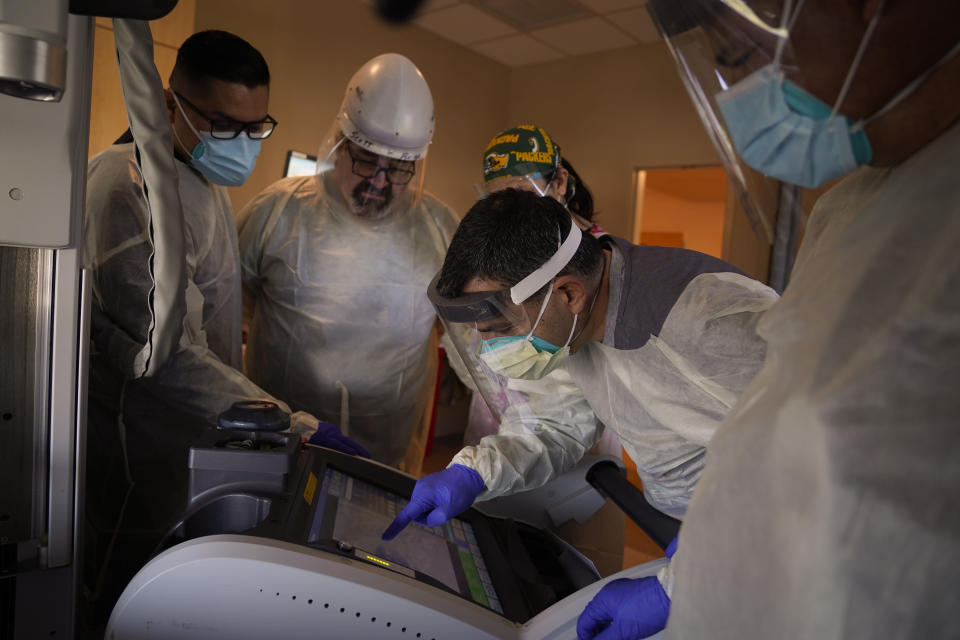 Dr. Mher Onanyan, center, examines an X-ray of a COVID-19 patient's lungs as he is surrounded by medical workers at Providence Holy Cross Medical Center in the Mission Hills section of Los Angeles, Tuesday, Dec. 22, 2020. (AP Photo/Jae C. Hong)