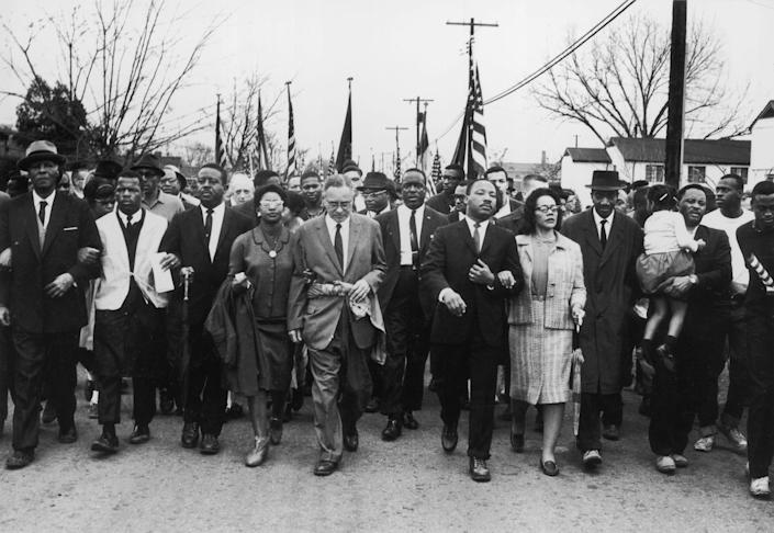 John Lewis (second from left) joins American civil-rights campaigner Martin Luther King Jr. and his wife Coretta Scott King in a march from Selma, Ala., to the state capital in Montgomery on March 30, 1965. | William Lovelace—Express/Getty Images