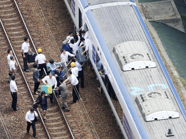 <p>Passengers descend from a train on the track after train service was suspended to check for damage following an earthquake in Takatsuki city, Osaka, western Japan, Monday, June 18, 2018. (Photo: Kyodo News via AP) </p>