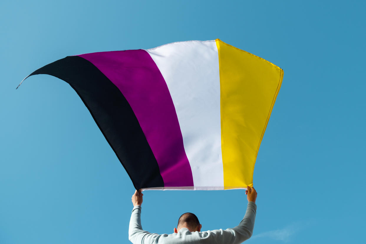 A person waves a Nonbinary Pride flag. (Getty Images)