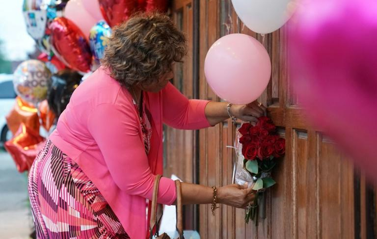 Brenda Averett places flowers at a temporary memorial set up for Aretha Franklin at New Bethel Baptist Church in Detroit