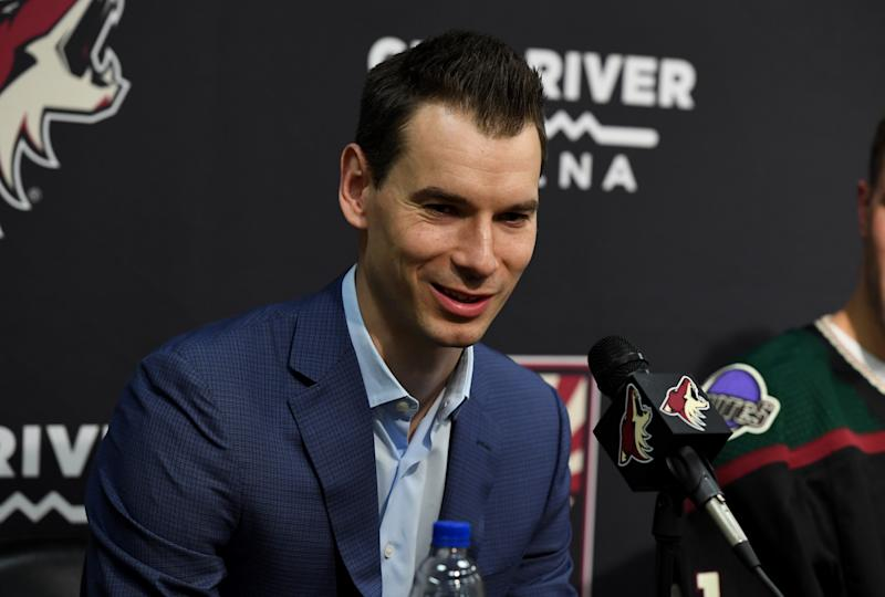 John Chayka smiles at a podium answering questions.