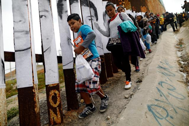 <p>Members of a caravan of migrants from Central America walk next to the border fence between Mexico and the U.S., before a gathering in a park and prior to preparations for an asylum request in the U.S., in Tijuana, Mexico April 29, 2018. (Photo: Edgard Garrido/Reuters) </p>