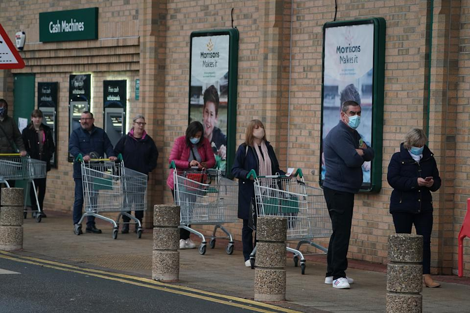 People queue outside a Morrisons supermarket in Whitley Bay, Tyne and Wear. Prime Minister Boris Johnson cancelled Christmas for almost 18 million people across London and eastern and south-east England following warnings from scientists of the rapid spread of the new variant of coronavirus. (Photo by Owen Humphreys/PA Images via Getty Images)
