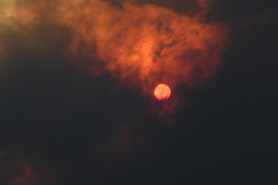 The sun shines through a thick cloud of smoke. The sky has turned red.