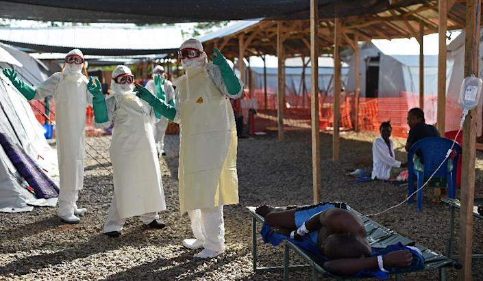 Health workers wearing personel protective equipment dance for Ebola patients sit in the Kenama treatment centre run by the Red Cross Society on November 15, 2014 (AFP Photo/Francisco Leong)