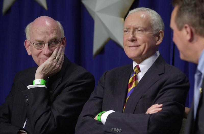 FILE - In this May 4, 2004, Utah Republican Sen.s Robert Bennett, left, and Orrin Hatch, center, talk on stage during the state Republican convention in Sandy, Utah. When the three-term Bennett lost re-election in 2010, it sent shock waves through the Republican Party and heralded a revolt that saw tea-party-backed candidates, like Christine O'Donnell, Sharron Angle and Marco Rubio, topple more established, mainstream Republicans. Disgruntled conservatives planted the seeds for Bennett's defeat, and now some of them hope to replicate their success against six-term Hatch Thursday, March 15, 2012, in Utah's Republican caucuses. (AP Photo/Douglas C. Pizac, File)
