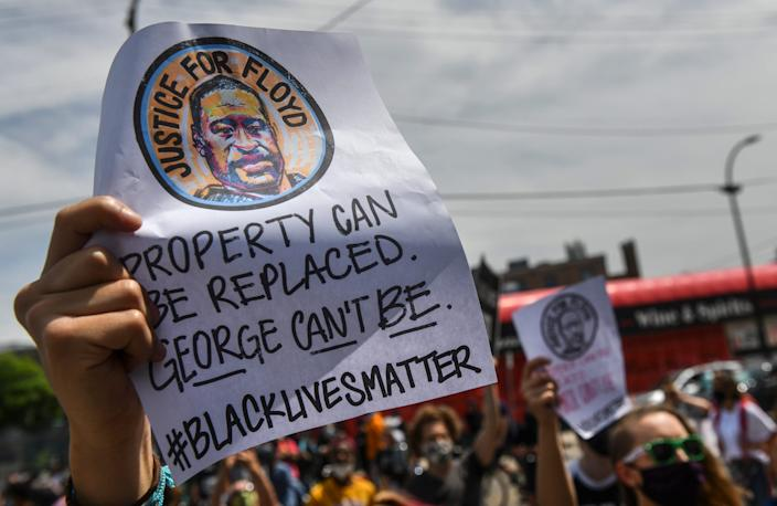 People hold signs near the Minneapolis Police Department's Third Precinct headquarters during protests following the death of George Floyd.