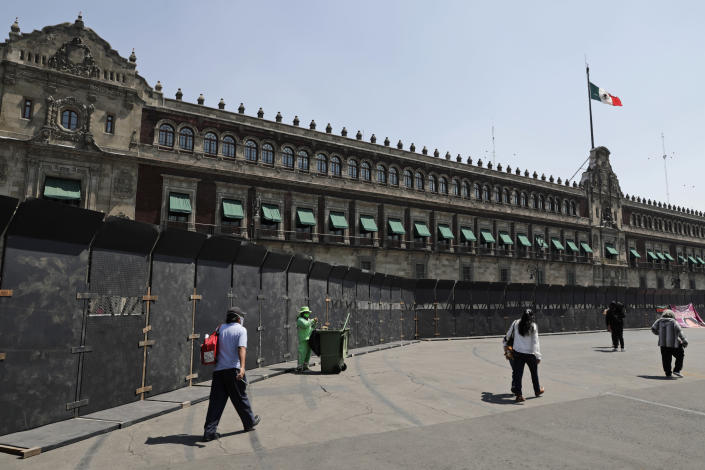 People walk past a perimeter fence set up in front of the National Palace in preparation for the upcoming International Women's Day demonstration, in Mexico City, Friday, March 5, 2021. Marked on March 8th, the day has been sponsored by the United Nations since 1975, to celebrate women's achievements and aims to further their rights. (AP Photo/Eduardo Verdugo)