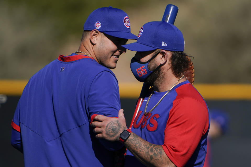 Chicago Cubs' Anthony Rizzo, left, shares a light moment with coach Mike Napoli during the team's spring training baseball workout in Mesa, Ariz., Monday, Feb. 22, 2021. (AP Photo/Jae C. Hong)