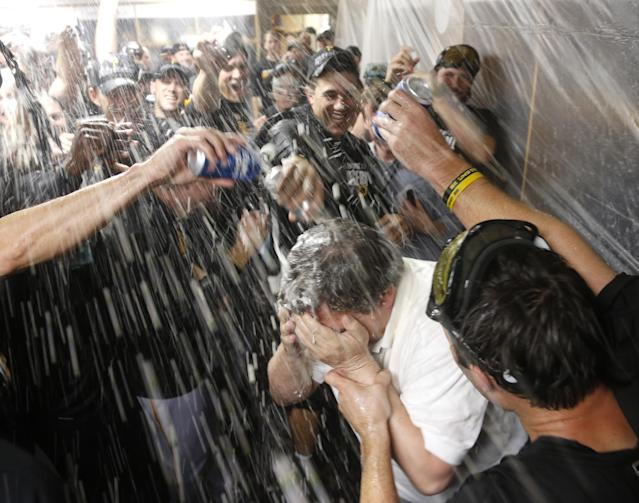 The Pittsburgh Pirates douse traveling secretary Greg Johnson with champagne and beer after a baseball game and 2-1 win over the Chicago Cubs Monday, Sept. 23, 2013, in Chicago. Johnson has been in his post for 30 years. (AP Photo/Charles Rex Arbogast)