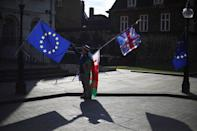 An anti-Brexit demonstrator waves EU, Union and Welsh flags opposite the Houses of Parliament in London, Britain, March 19, 2018. REUTERS/Hannah McKay