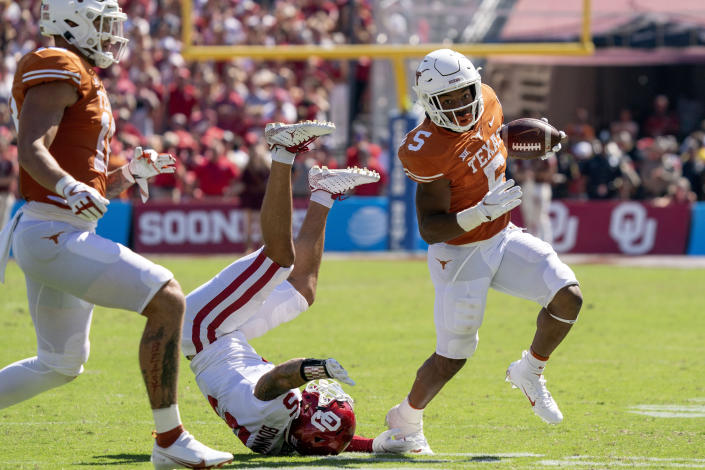 Texas running back Bijan Robinson (5) runs past Oklahoma defensive back Billy Bowman (5) during the first half of an NCAA college football game at the Cotton Bowl, Saturday, Oct. 9, 2021, in Dallas. (AP Photo/Jeffrey McWhorter)