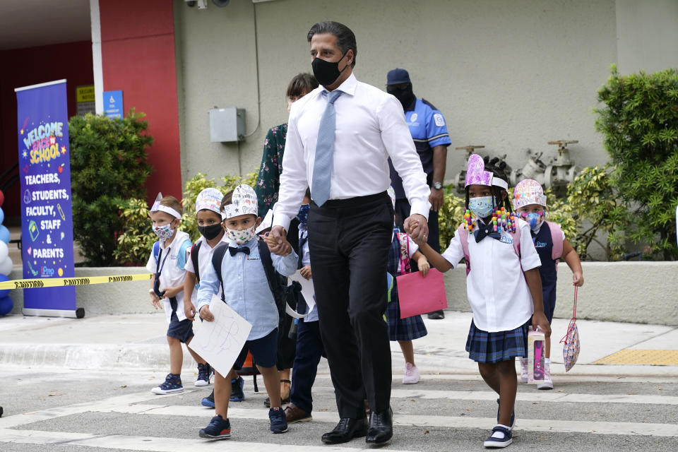 FILE- In this Aug. 23, 2021, file photo, Miami-Dade schools Superintendent Alberto Carvalho, center, walks with students Oliver Angel, left, and Ariah Olawale, right, outside of iPrep Academy on the first day of school, Monday, Aug. 23, 2021, in Miami. The on-again, off-again ban imposed by Republican Gov. Ron DeSantis to prevent mandating masks for Florida school students is back in force. The 1st District Court of Appeal ruled Friday, Sept. 10, 2021, that a Tallahassee judge should not have lifted an automatic stay two days ago that halted enforcement of the mask mandate ban. (AP Photo/Lynne Sladky, File)