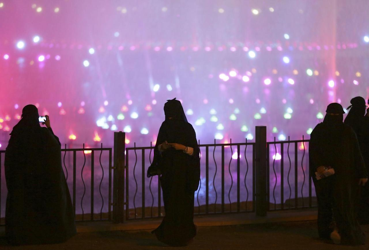 FILE -- In this March 29, 2014, file photo, a Saudi woman takes photographs in a park during celebrations to mark the worldwide Earth Hour in Riyadh, Saudi Arabia. Saudi Arabia has issued and published new guidelines Tuesday, April 12, 2016 to define and curtail powers of the kingdom's religious police. The force's members, known as Mutawas, are not allowed to chase people down the street or demand to see a person's ID. They are tasked with ensuring people observe the kingdom's ultraconservative Islamic codes but have been criticized for sometimes intrusive tactics. (AP Photo/Hasan Jamali, File)